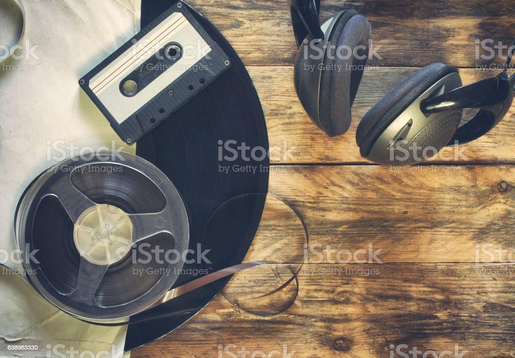 old vinyl record, audio cassette, tape bobbin and headphones stock photo