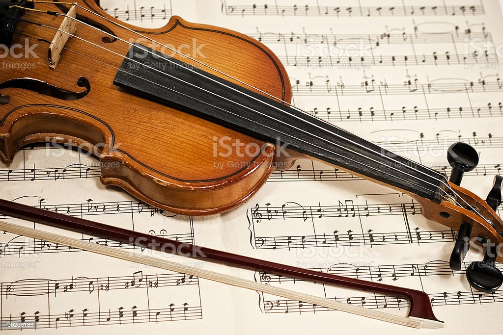 Old violin and bow on musical notes stock photo