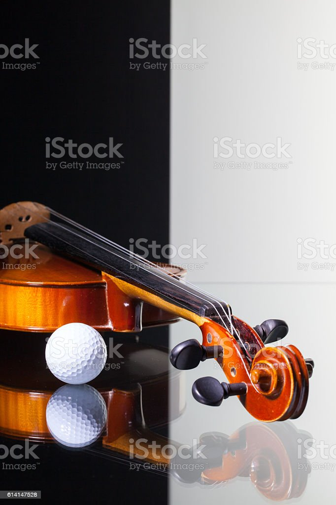 Old violin and golf ball on black and white background stock photo