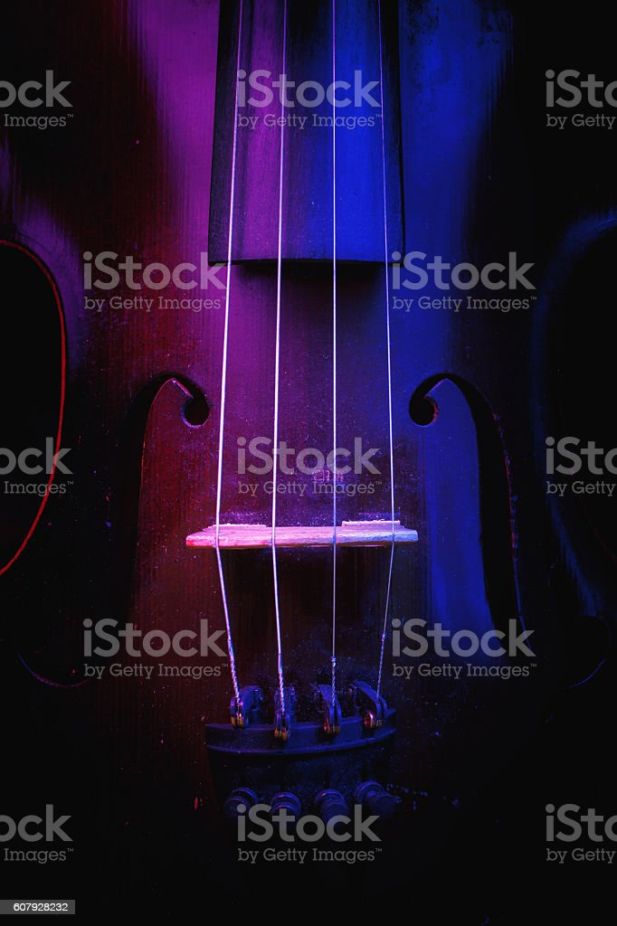 Old Violin Illuminated in Blue and Purple stock photo