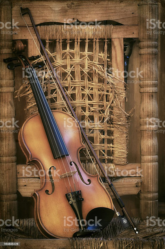 Old Violin lying on a ruined chair royalty-free stock photo