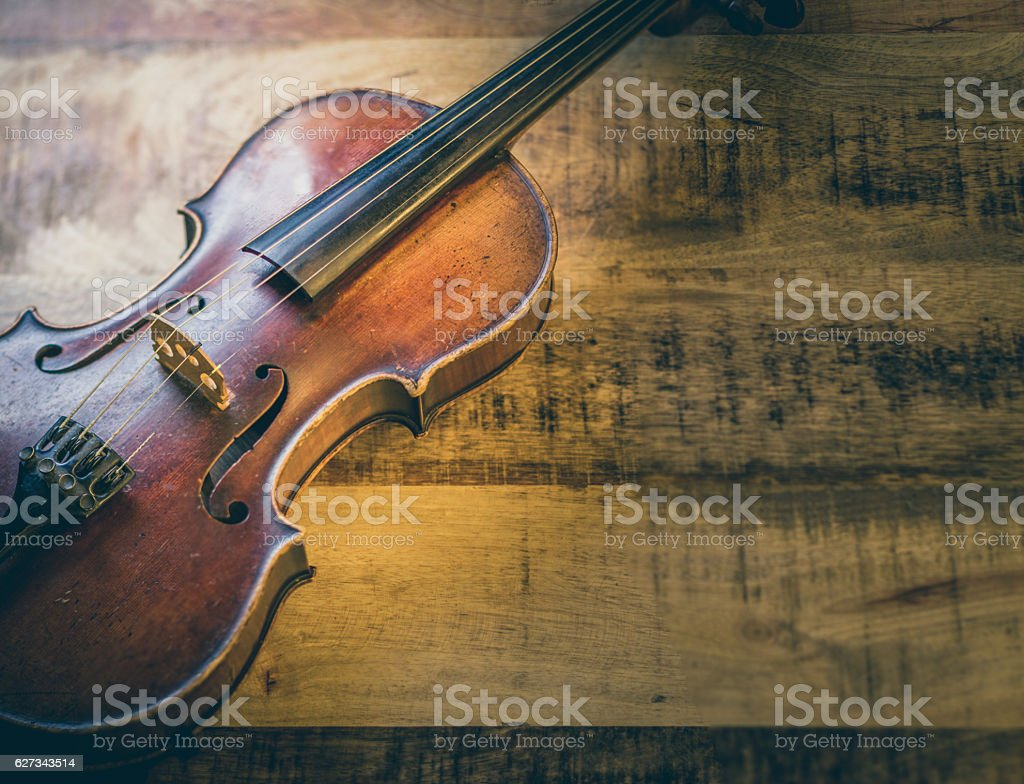 Old violin on a wooden background stock photo