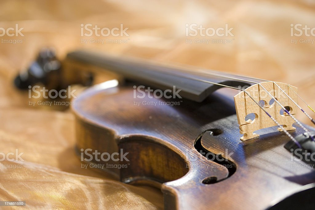 Old violin on golden fabric royalty-free stock photo