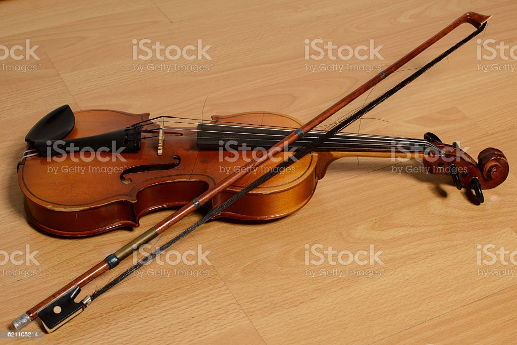 Old violin with a bow lies on wooden bench stock photo