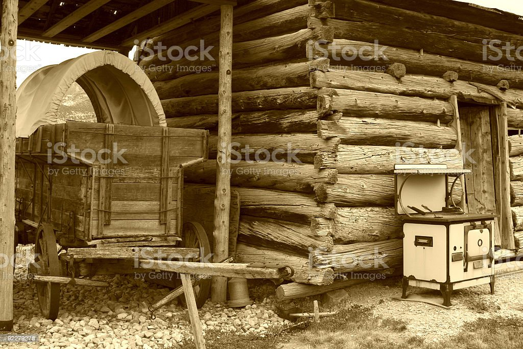 Old Wagon and Log Cabin with Stove out front. royalty-free stock photo
