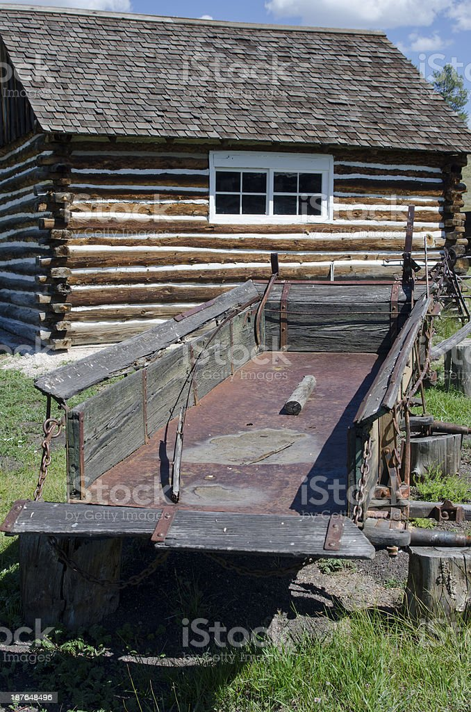 Old Wagon Bed and Log Cabin stock photo