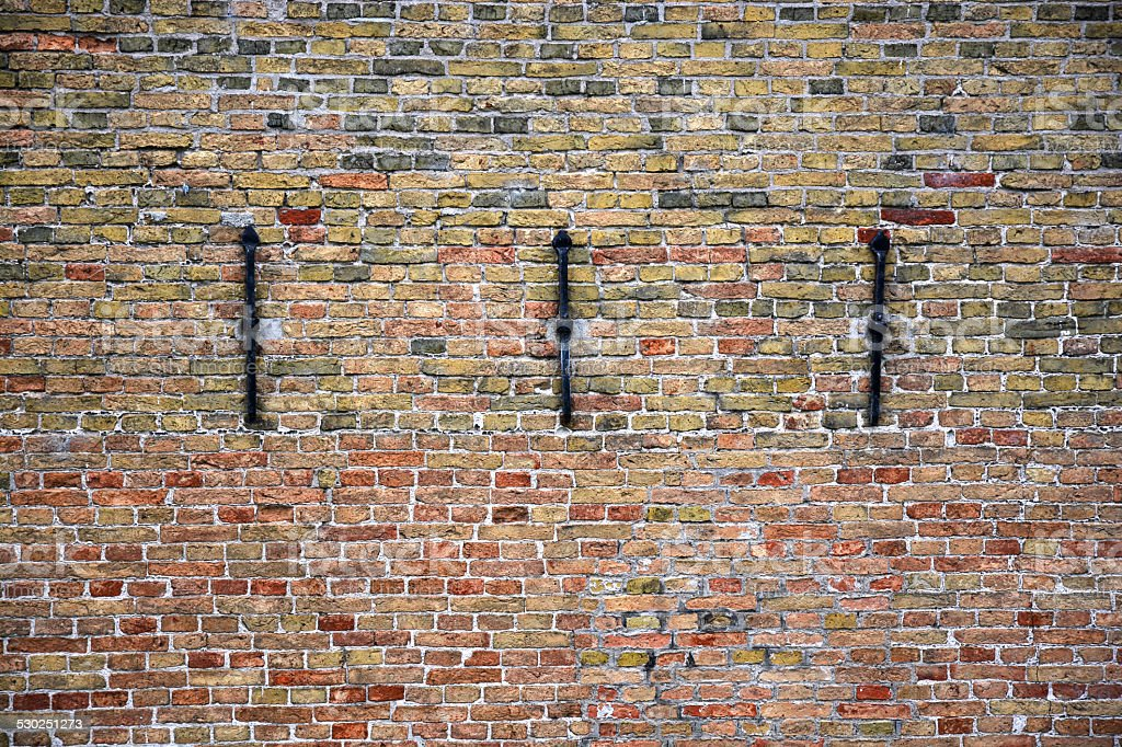 Old wall made of little bricks with cast iron stock photo