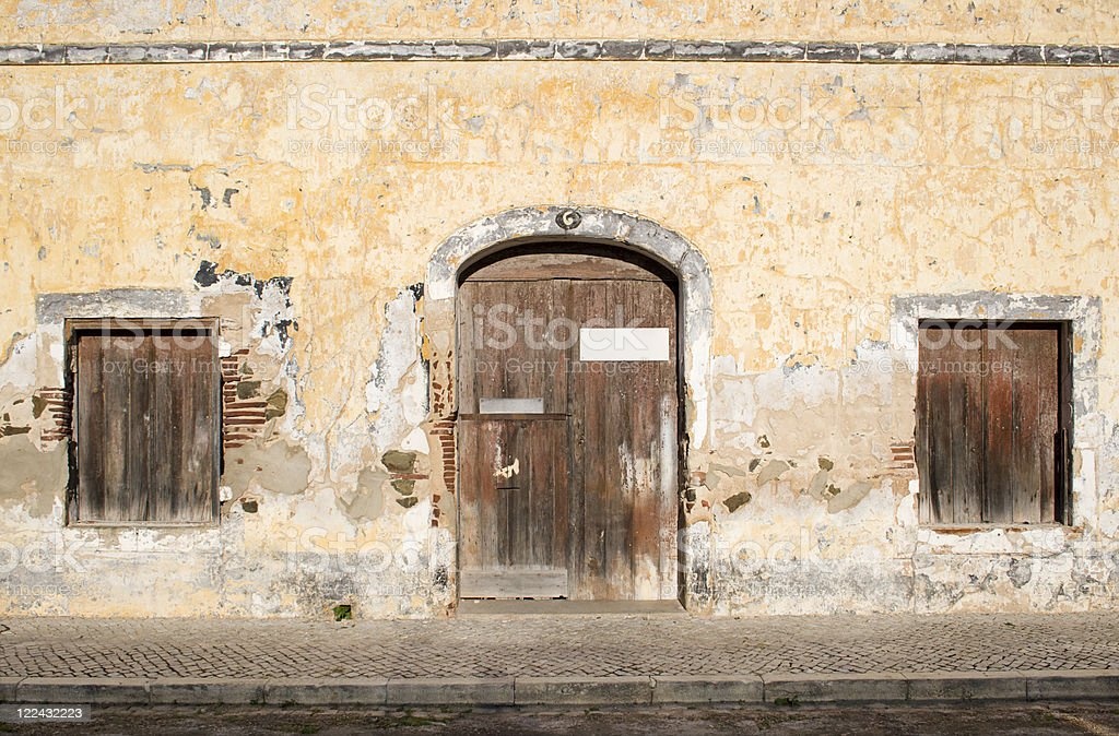 Old wall with two windows and door royalty-free stock photo
