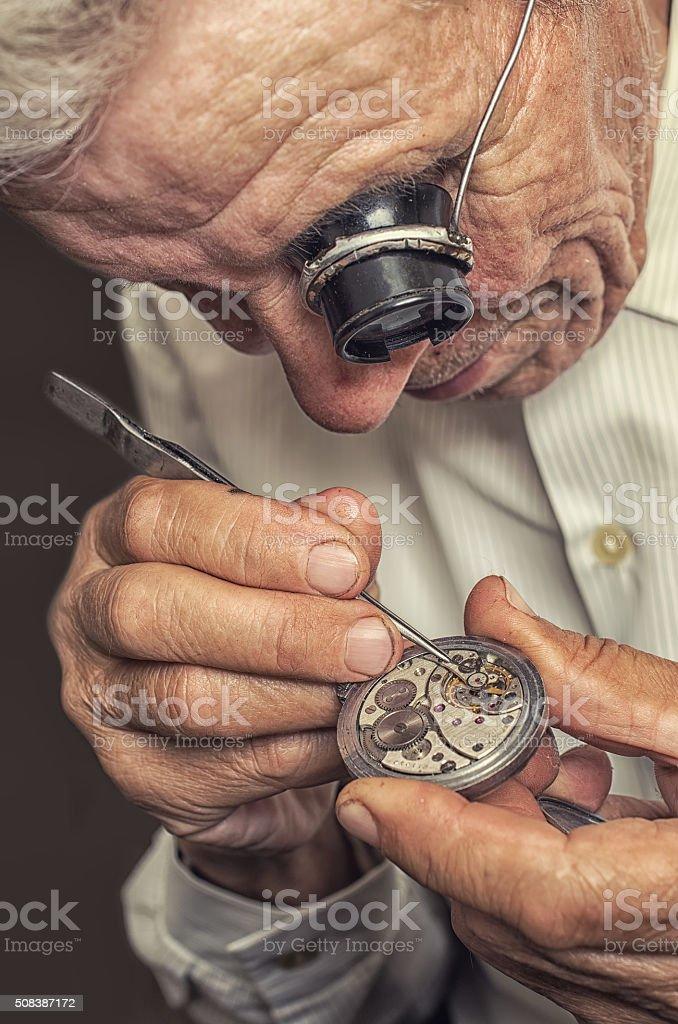 old watchmaker repairing clocks stock photo