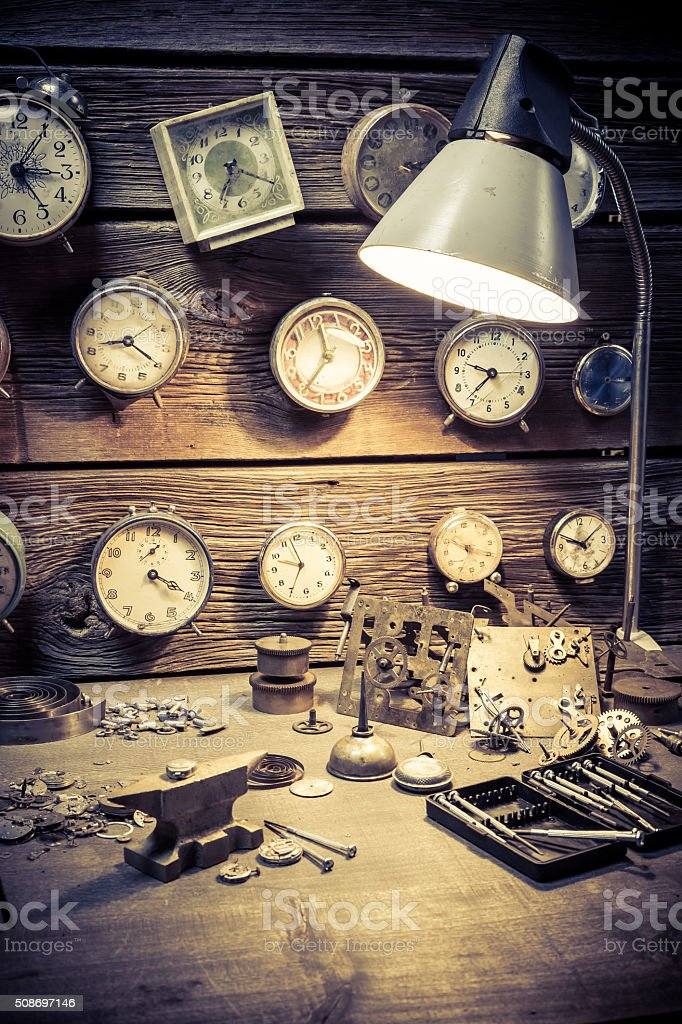 Old watchmaker's workshop with damaged clocks stock photo
