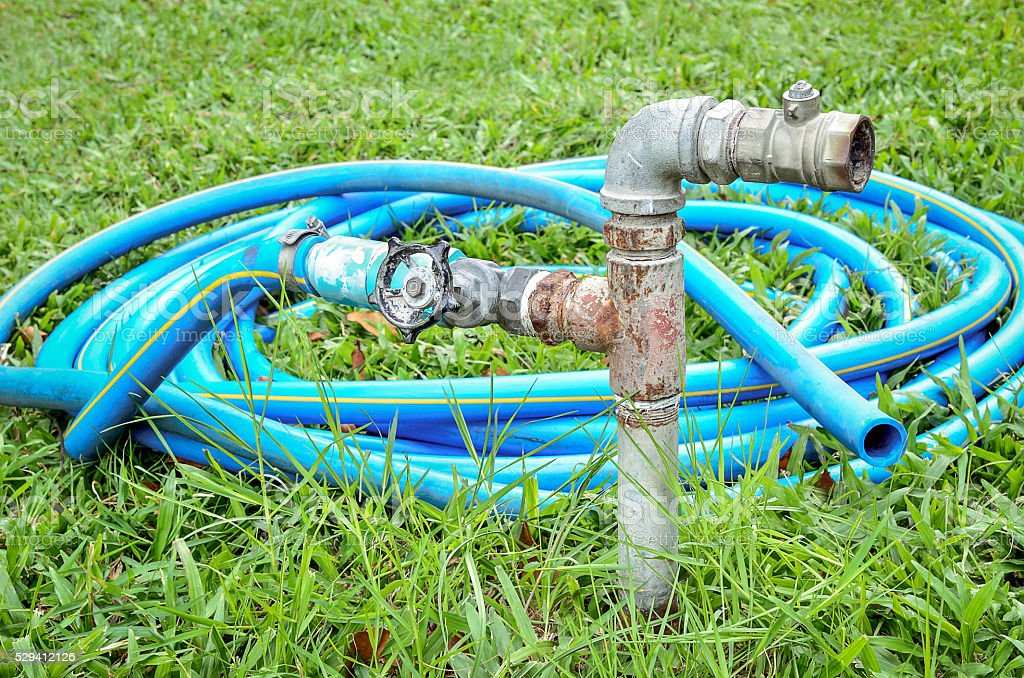 Old water valve with blue rubber water hose stock photo