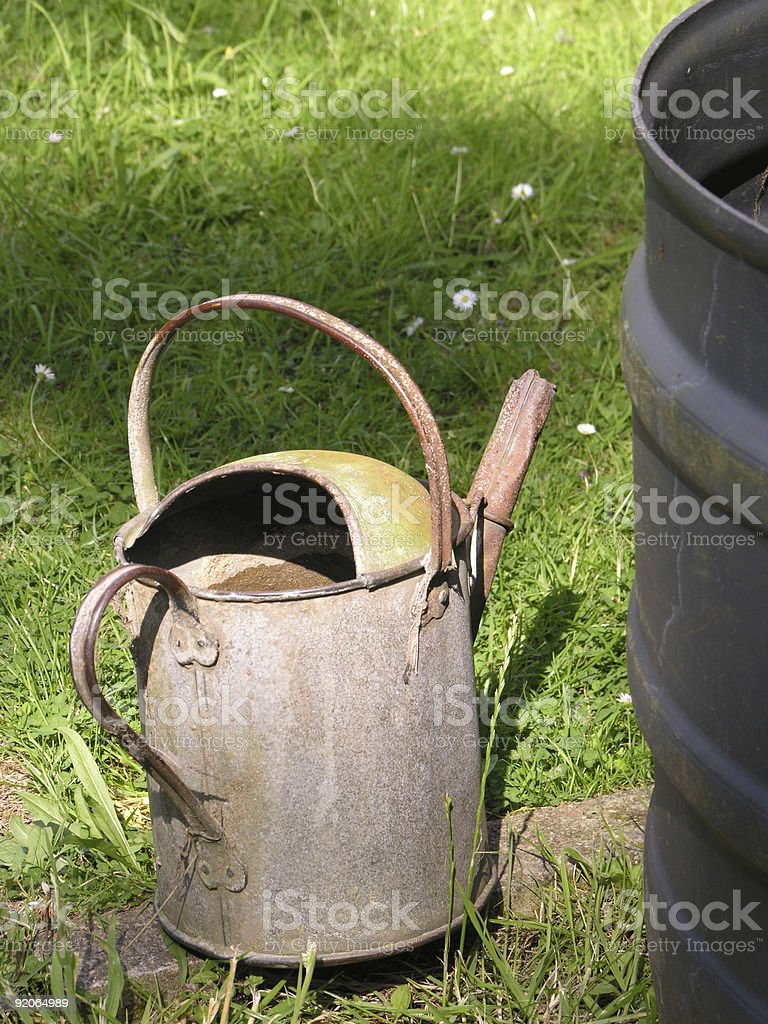 Old watering can and water butt royalty-free stock photo