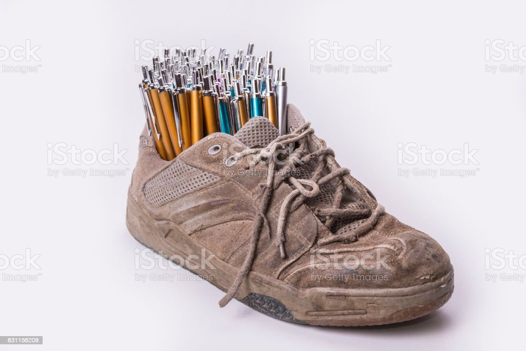 Old wear out shoe stock with lot of pens stock photo