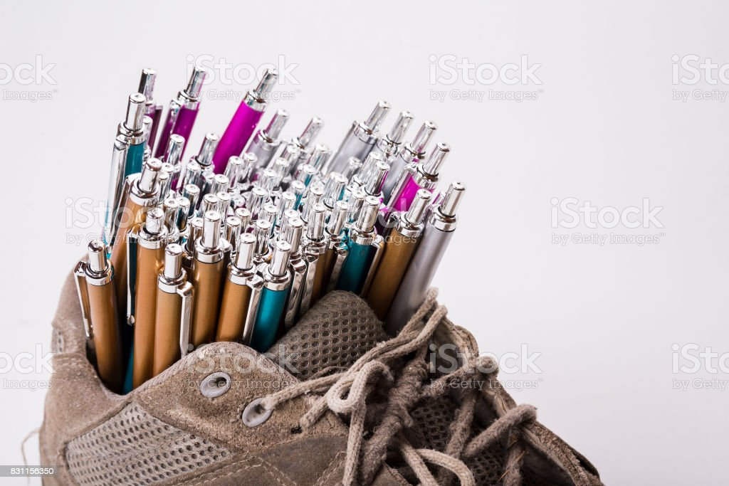 Old wear out sneaker is used like a pen holder stock photo
