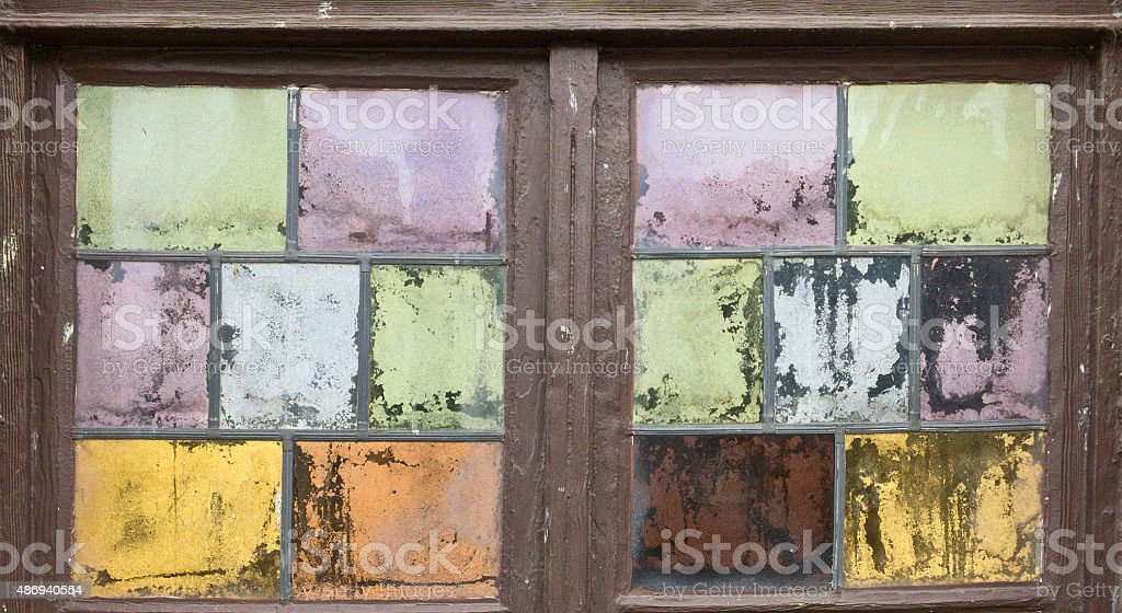 old weatherd window with pastel colored window glass stock photo