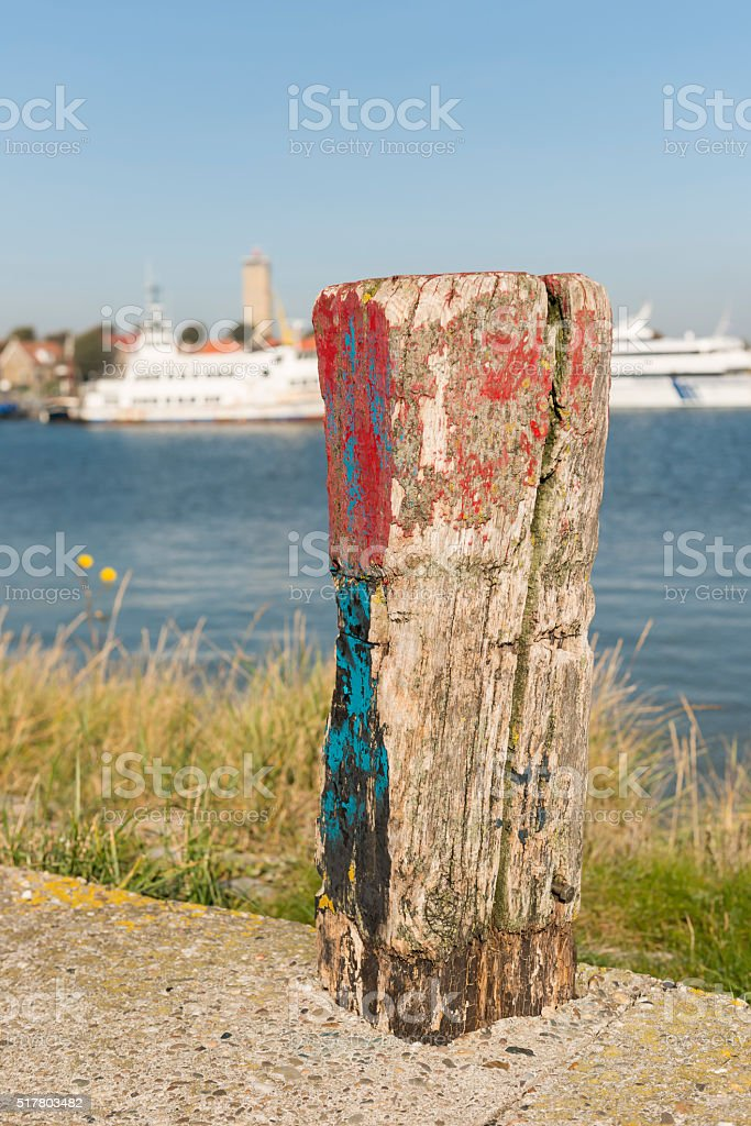 Old weathered and beautifully colored mooring pole. stock photo