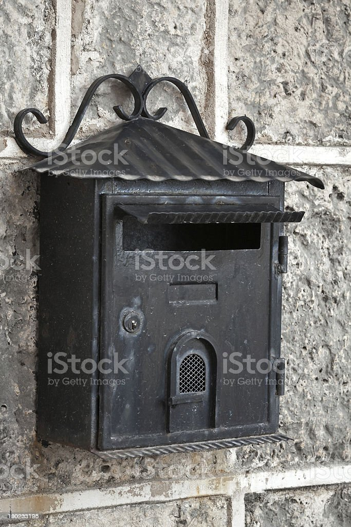 Old weathered black metal mailbox mounted on gray stone wall royalty-free stock photo