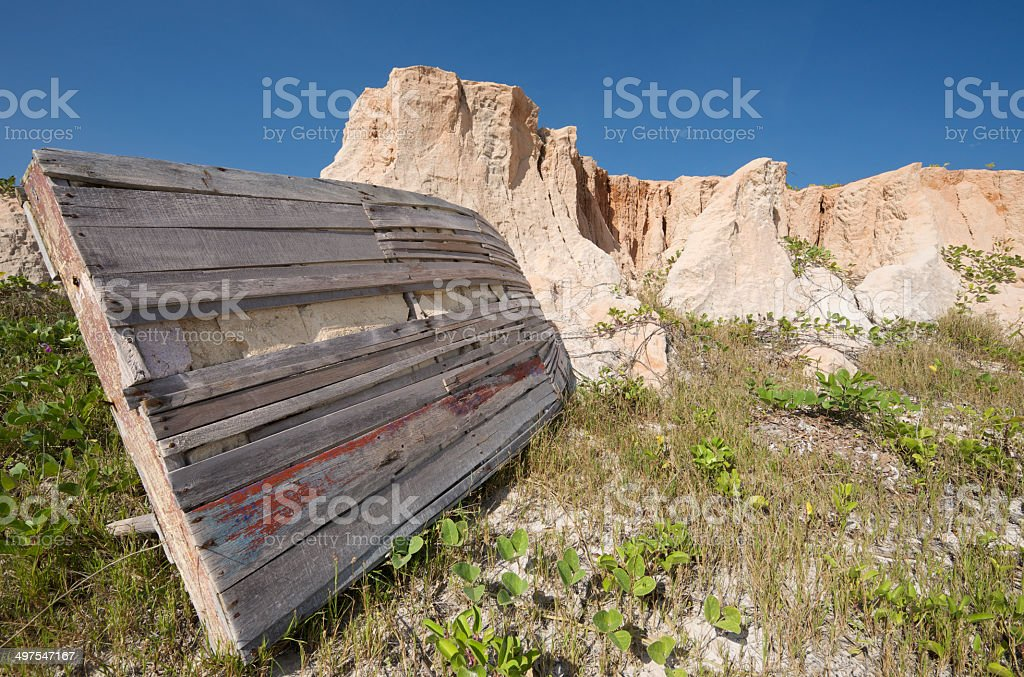 Old weathered Jangada and red cliffs of Canoa Quebrada, Brazil stock photo