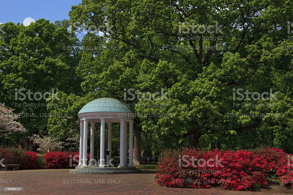 Old well at Chapel Hill among green trees and red flowers stock photo