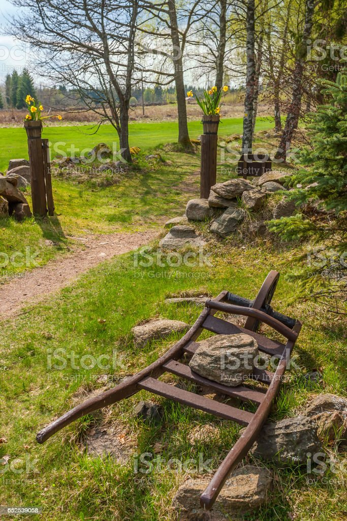 Old wheelbarrow with a stone in a garden in spring stock photo