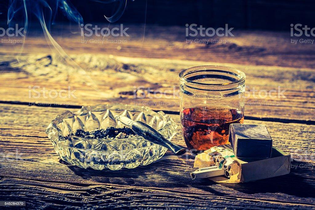 Old whiskey, cigarettes and ashtray stock photo
