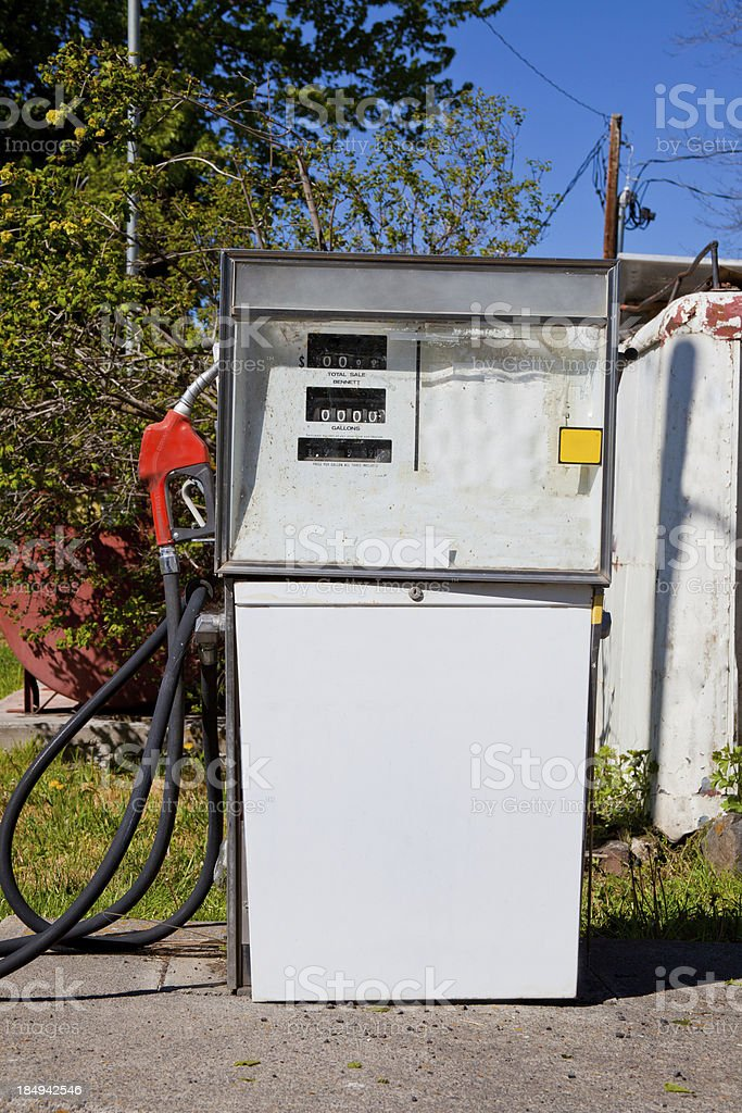 Old white gas station in a deserted place near trees stock photo