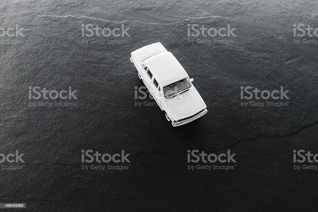 Old, white toy car on the black ground, directly above stock photo