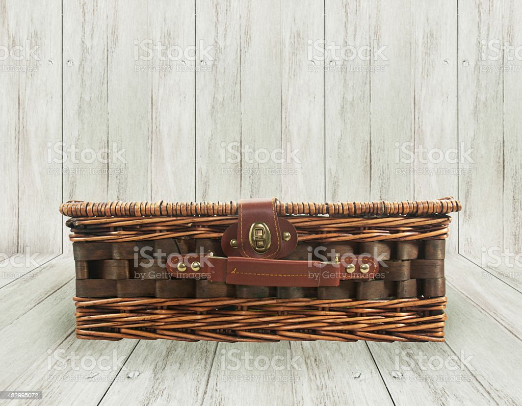 Old wicker bag on wooden background. stock photo