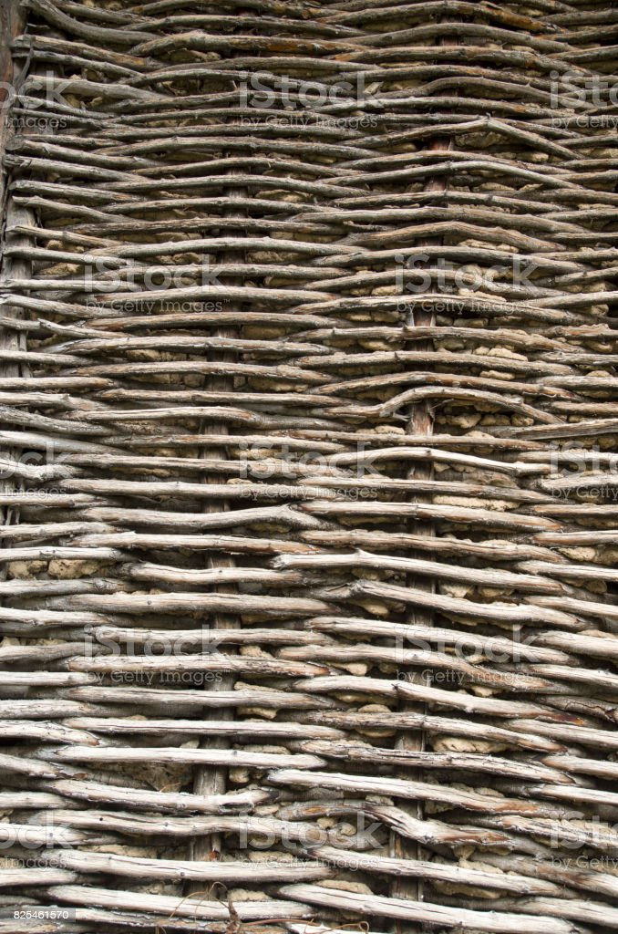 Old wicker wooden wall plastered with mud stock photo