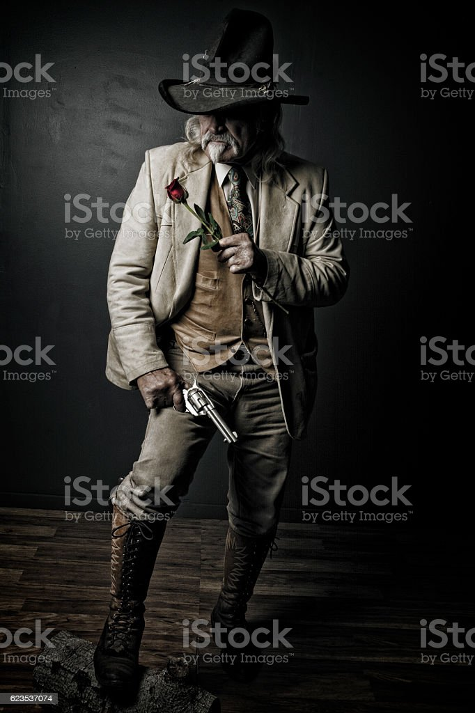 Old Wild West Cowboy Gunslinger With Red Rose stock photo