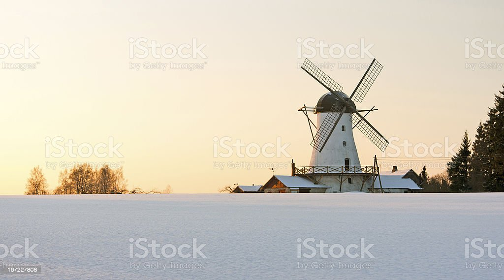 Old windmill behind snow field royalty-free stock photo