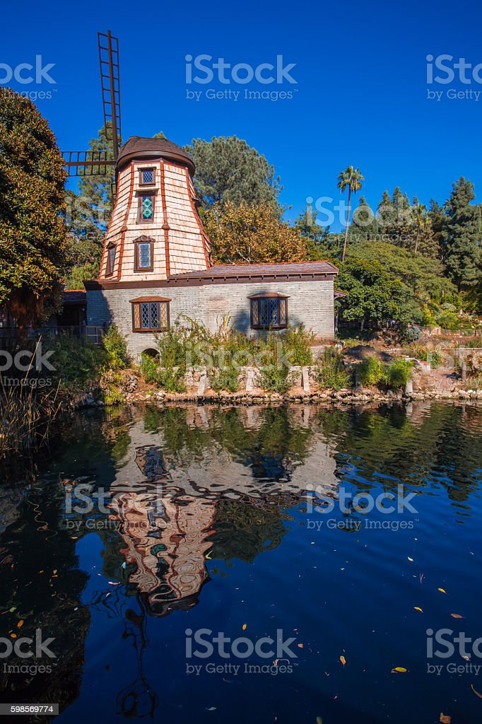Old windmill in front of lake stock photo
