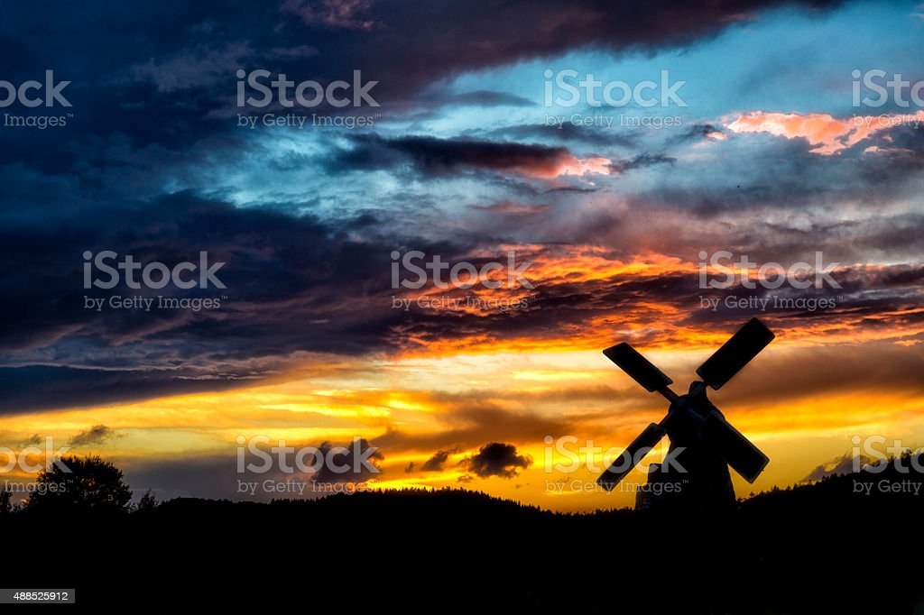 Old windmill in sunset and dramatic cloudscape stock photo