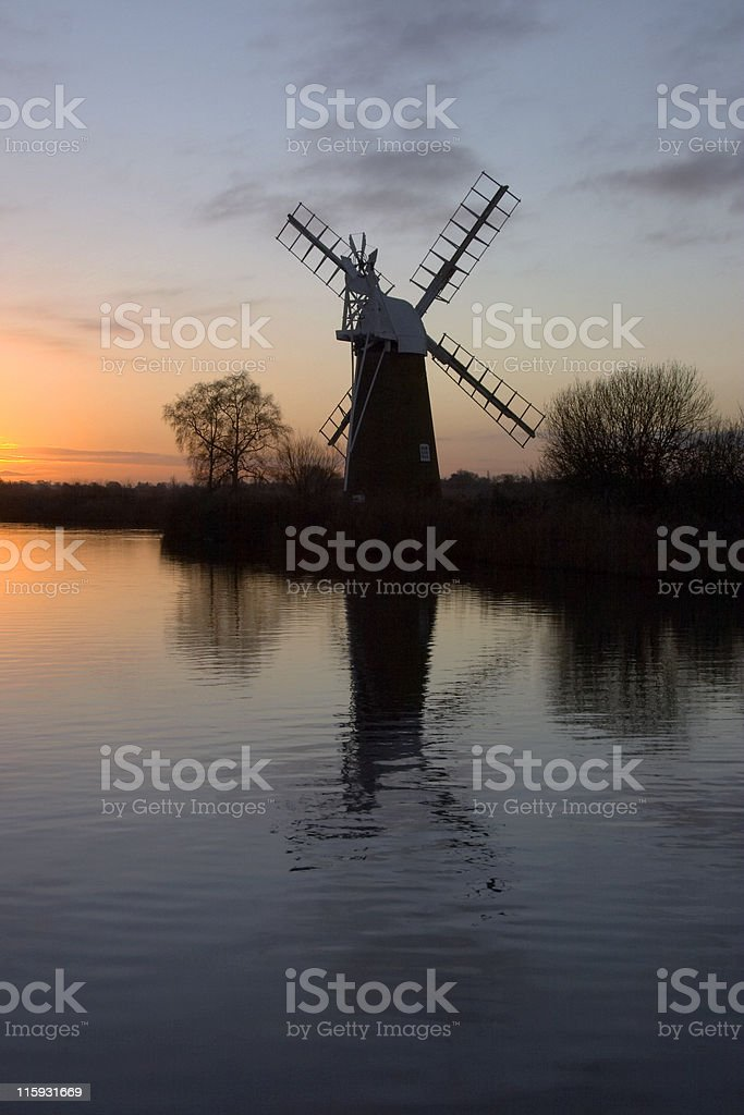 Old windmill on the norfolk broads at sunset royalty-free stock photo