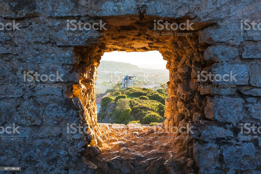 Old Windmill through Window in Fortress Wall royalty-free stock photo