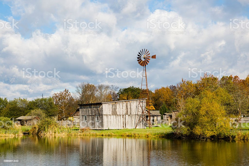 Old Windmill, Wooden Barn and Cloud Filled Skies stock photo