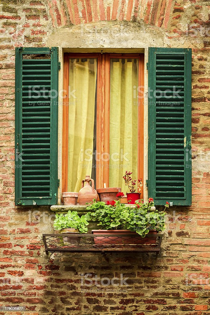 Old window decorated with flower pots and flowers royalty-free stock photo