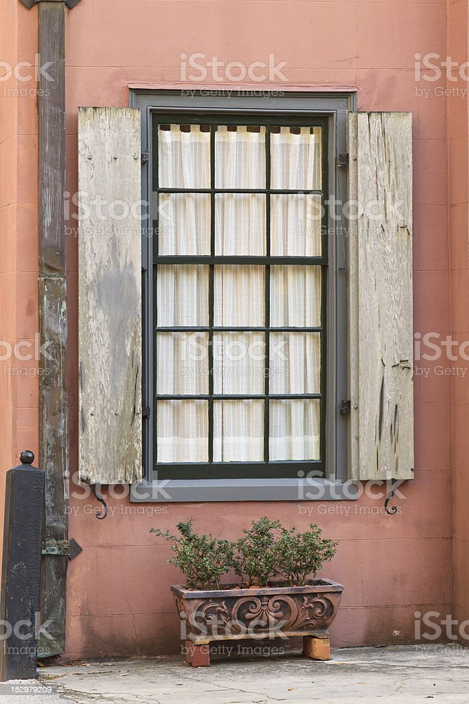 Old Window, Shutters, and Potted Plant On Historic Building stock photo