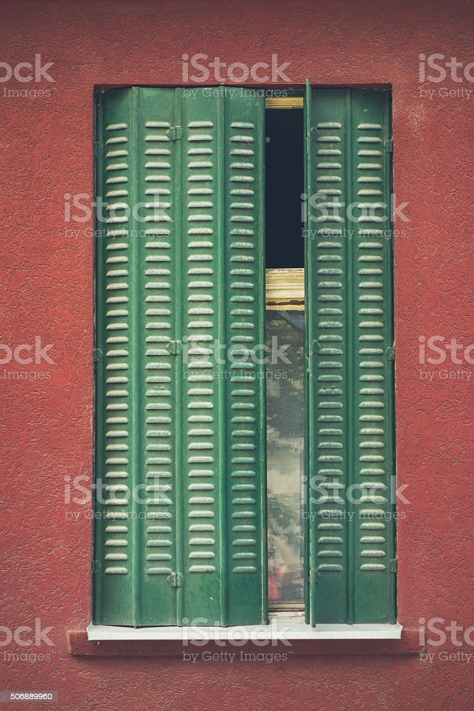 Old window with green blinds and reddish wall stock photo
