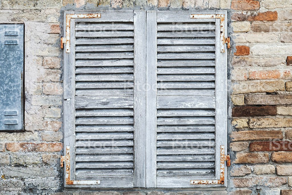 Old window with white closed wooden shutters stock photo