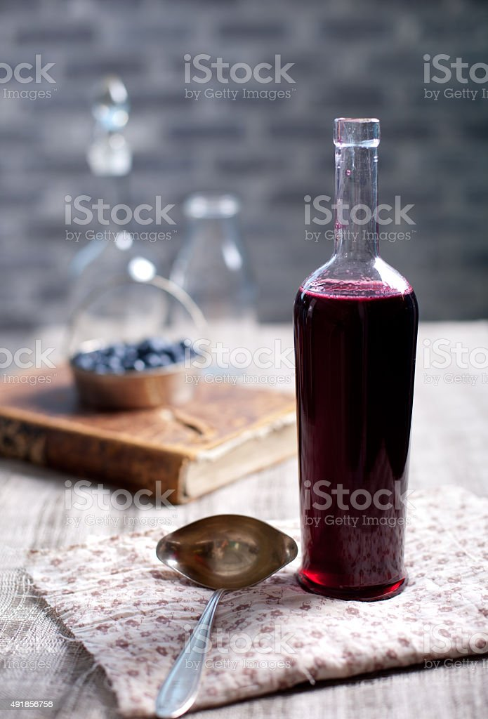 Old wine bottle with homemade berry vinegar. stock photo