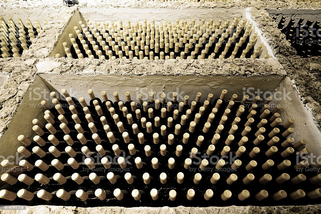 Old wine bottles in cellar. Spyder web visible. Old wine stock photo