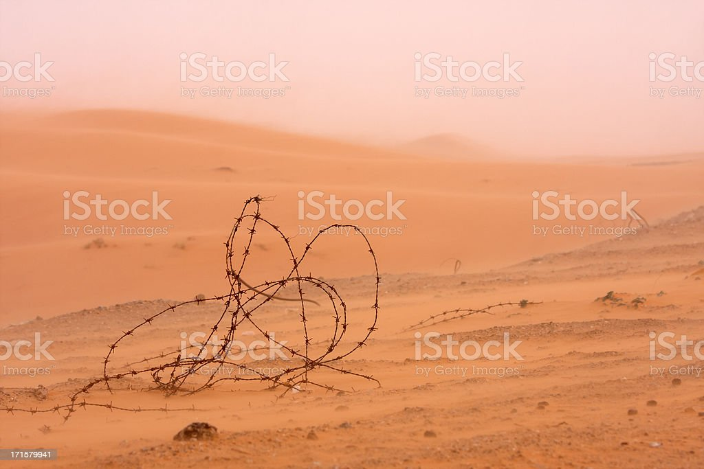 old wire fence in a sand storm near dubai stock photo