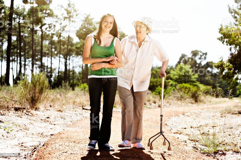 Old woman and young caregiver companion walking happily in sunshine stock photo