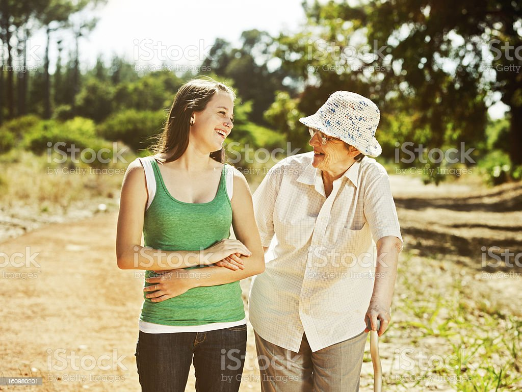 Old woman and young granddaughter or caregiver enjoy forest walk stock photo