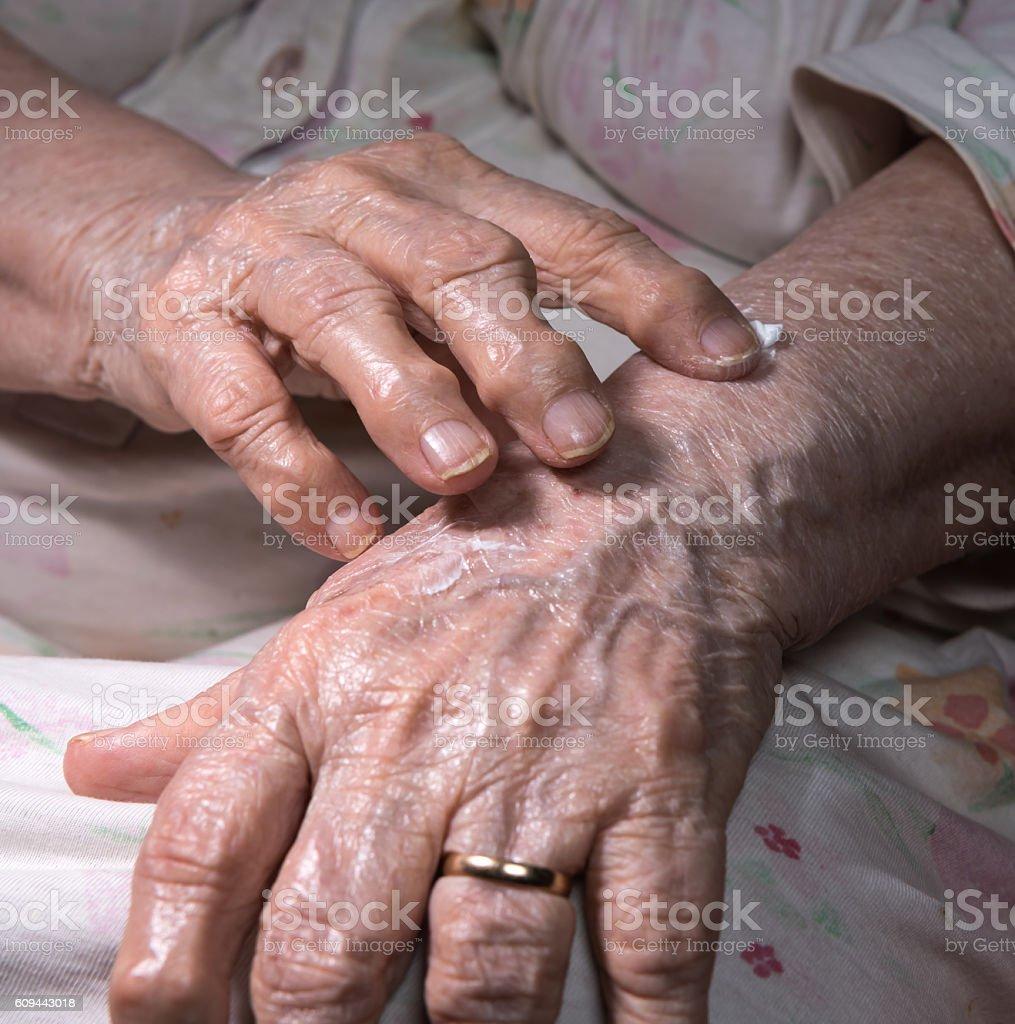 Old woman applying hand cream stock photo