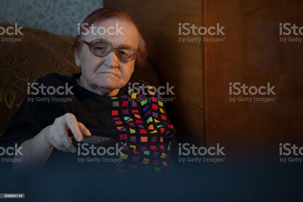 Old woman at home watching TV and changing channels stock photo
