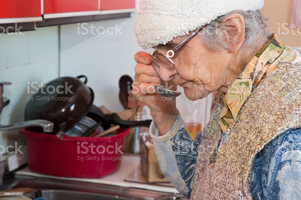 Old woman at tasting of the eat stock photo