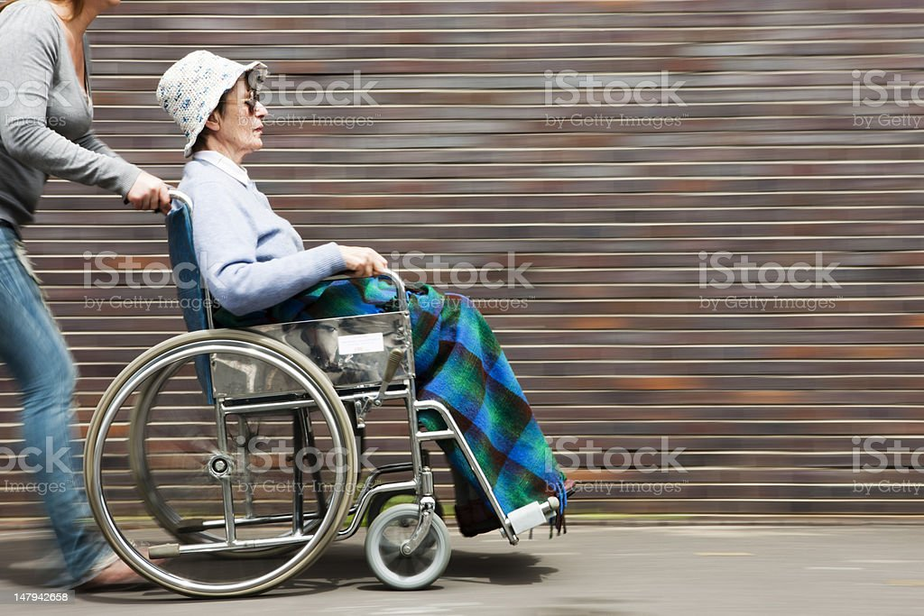 Old woman being pushed in wheelchair with motion blur royalty-free stock photo