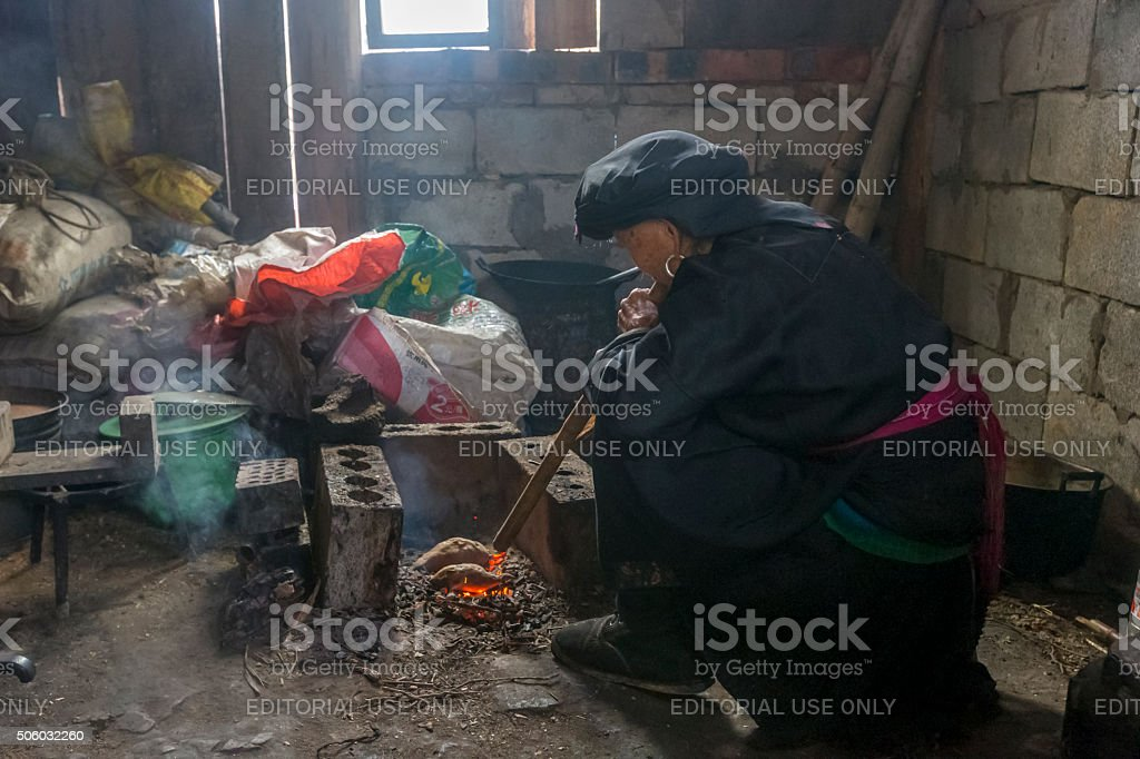 Old woman blowing pipe to bake the sweet potato,  China stock photo
